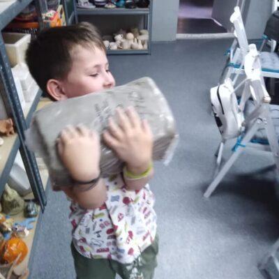chłopiec niesie kawałek gliny