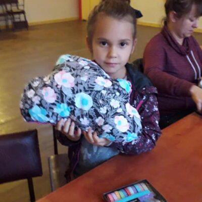 dziewczynka trzyma uszytą poduszkę