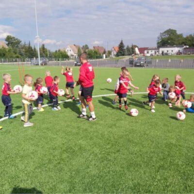 Trener z uczniami na boisku