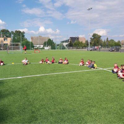 Dzieci siedzą w kole z piłkami
