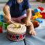 Chłopiec bawiący się drewnianym bębenkiem
